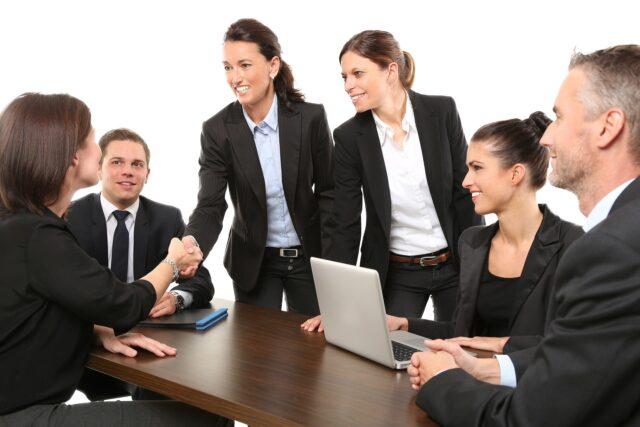 Sex kostymklädda personer runt ett bord.